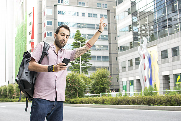 Young White Man Holding A Cellphone Hailing Uber Taxi