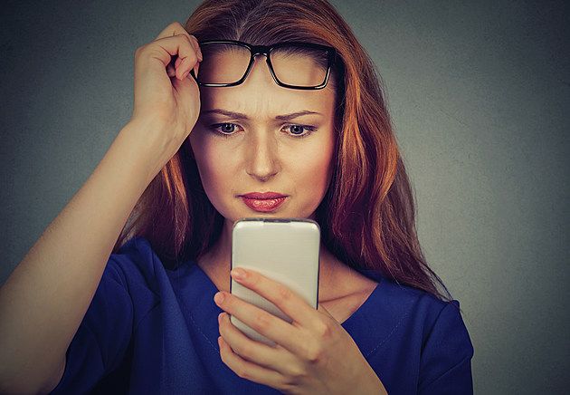 woman with glasses having trouble seeing cellphone vision problems